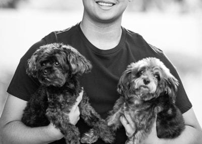 monochrome photo of boy holding 2 puppies