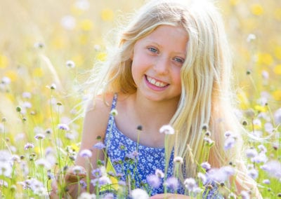 blond girl in a meadow holding a flower