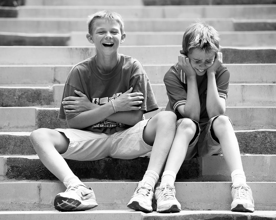 monochrome photo of 2 boys sitting on steps and sharing a joke