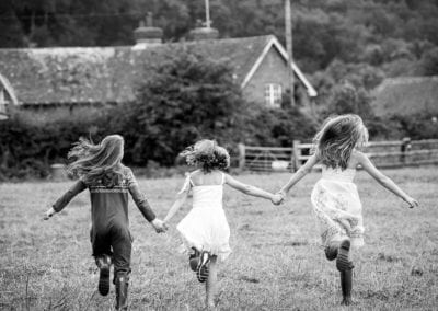 monochrome photo of 3 sisters running