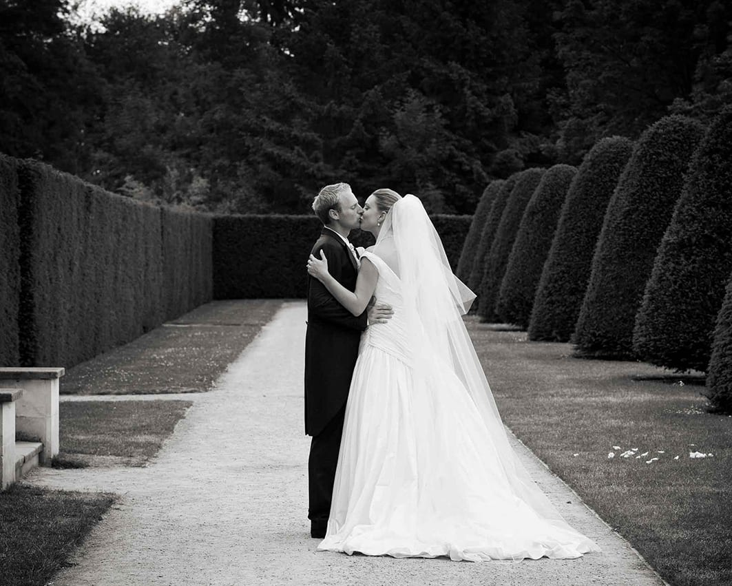 Black and white photo of a recently married couple kissing in a beautiful garden