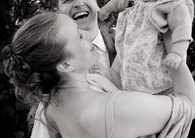 bride and groom laughing with baby on their wedding day